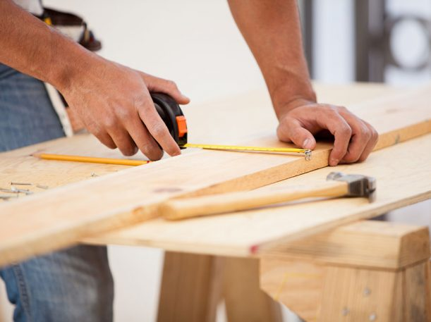 Carpenter measuring wood for a residential project.
