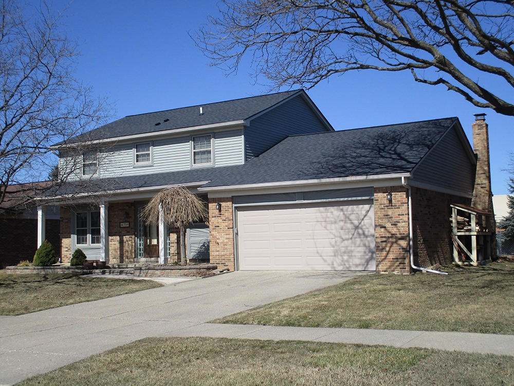 After photo of home with new roofing, siding, and gutters.