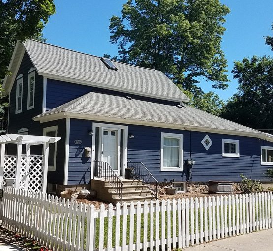 Residential siding job with new James Hardie Fiber Cement Siding and Gutters. Blue farmhouse in Milford, Michigan.
