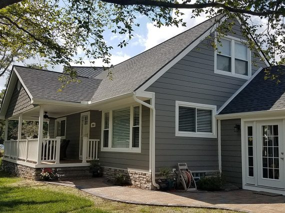 Exterior remodel with roofing, siding, front porch addition, James Hardie Fiber Cement Siding, stone, and windows. West Bloomfield, Michigan.