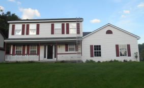 Before photo of white house with maroon shutters in Oxford, Michigan.