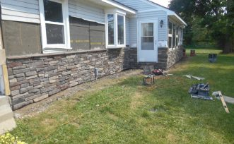 Exterior remodeling project including siding, gutters, and stone work. Ortonville, Michigan.