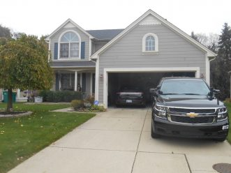 Before photo of light grey home with dated shutters and scalloped accent shingles in Auburn Hills, Michigan.