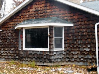 Before photo of cedar shingle house in poor condition located in Dryden, Michigan.
