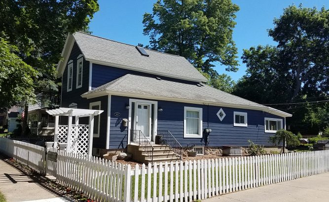 Exterior remodel with new James Hardie Fiber Cement Siding and Gutters. Blue farmhouse in Milford, Michigan.