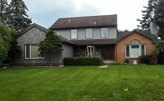 Home in Troy, Michigan, Grennan Construction completed an install of Monogram Dutch Lap siding in charcoal grey with bronze gutters. NovikStone accent wall completed using Fieldstone panels.